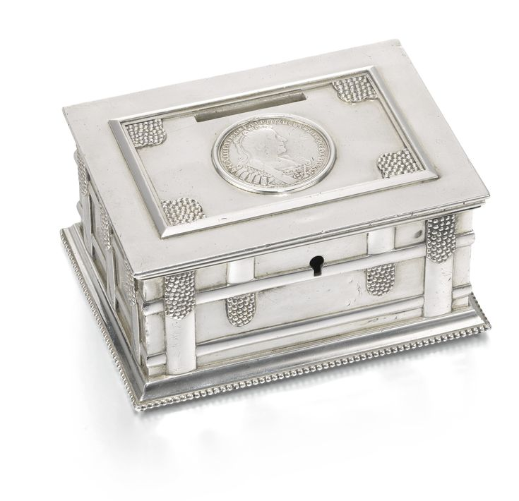 A Fabergé silver money box, Moscow, 1908-1917, the lid inset with 1 poltina silver coin of Empress Anna Ioannovna (dated 1732), the sides with trompe l'oeil casket straps, gilt interior.