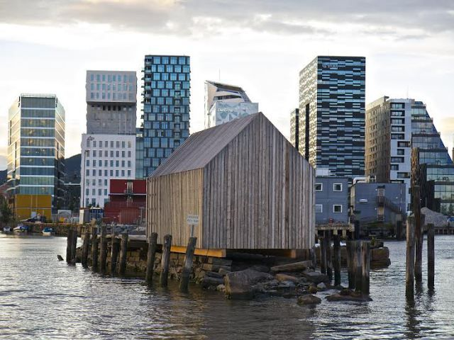 small wooden house in front of the barcode buildings, bjørvika