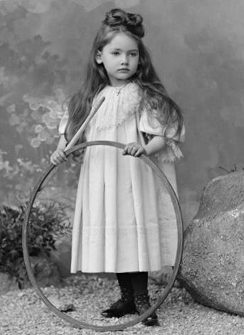 Beautiful little girl with an angelic face and long dark hair tied up in a bow, holding a hoop toy. Antique Victorian cabinet card photo, 1890s.
