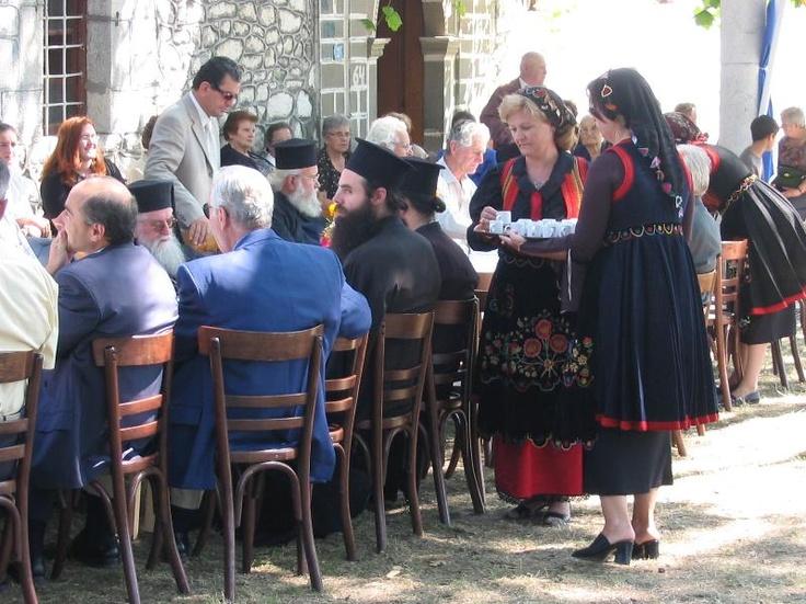 Padhes, Griekenland, 17 augustus 2003.  Na een herdenkingsceremonie brengen vrouwen in klederdracht koffie naar priesters en andere officiele genodigden.