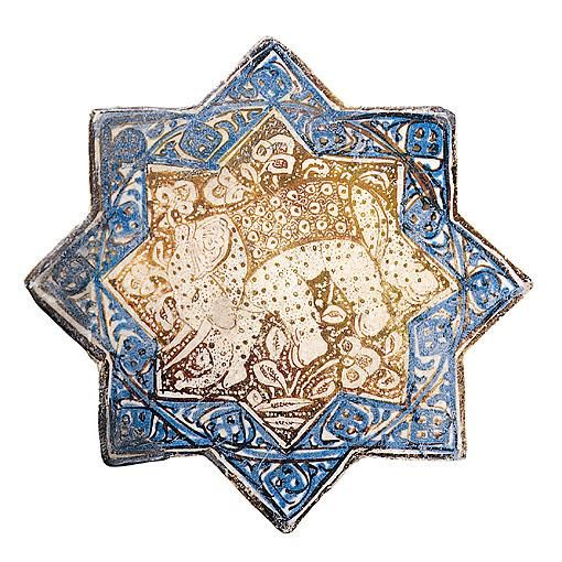 A Kashan lustre-decorated star-form pottery tile  the eight-pointed form decorated in lustre, cobalt blue and turquoise with a design of a pair of seated figures flanking a cypress tree, within a border of cursive calligraphy