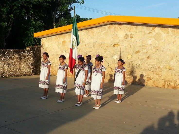 Escolta de una escuela primaria usando el hipil yucateco como prenda de gala para portar la bandera