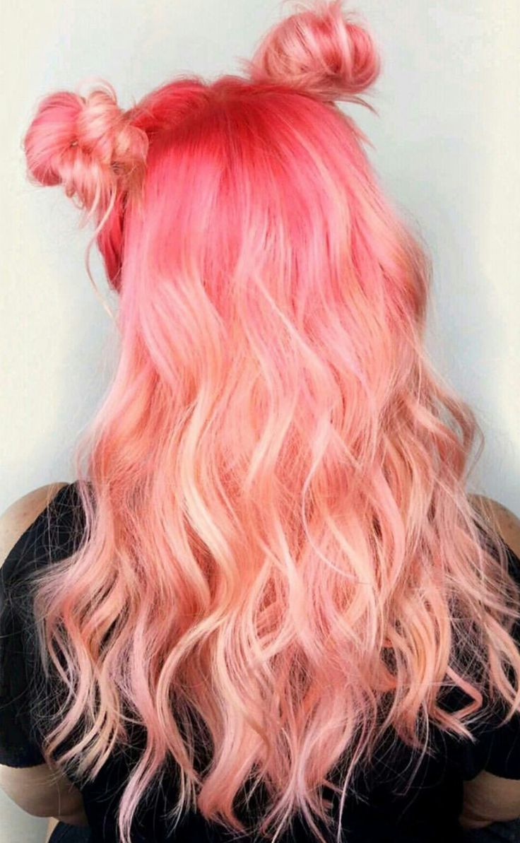 Peach pink hair color inspo with space buns for medium length hair in soft curls | Dark pink roots to pale pink ombre