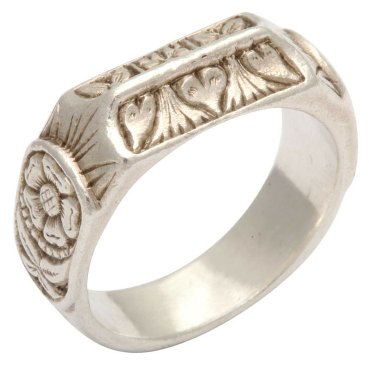 Rarely are rings found from the medieval ages. At this time nobility wore jewels of gold and silver. Base metal was worn by other classes. The English Empire was ruled by Henry V11 when this ring was worn. Symbolizing the amalgamation of the Lancaster and York noble factions, this silver band traveled time well. The bezel is composed of two concave rectangular panels engraved with hearts and Tudor Roses...circa 15th century