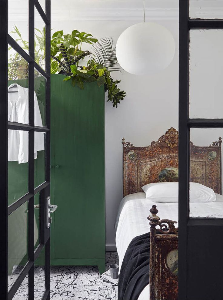 Eclectic bedroom with a green wardrobe and distressed headboard