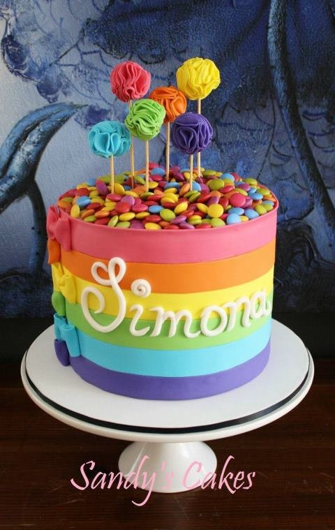 Rainbow cake with colorful cake pops. I love he they did the design on the cake pops...interesting