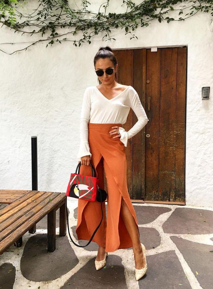 Look da Lalá Noleto: blusa de manga comprida branca com mangas volumosas e calça laranja desconstruída, ótimo para usar no verão