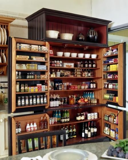 """The """"larder"""" was used to store food and cooking implements.  Unlike a dresser, it had no work surface and was used just for storage. This custom larder by Venegas & Company makes use of every square inch of space, including door racks, for efficient storage."""