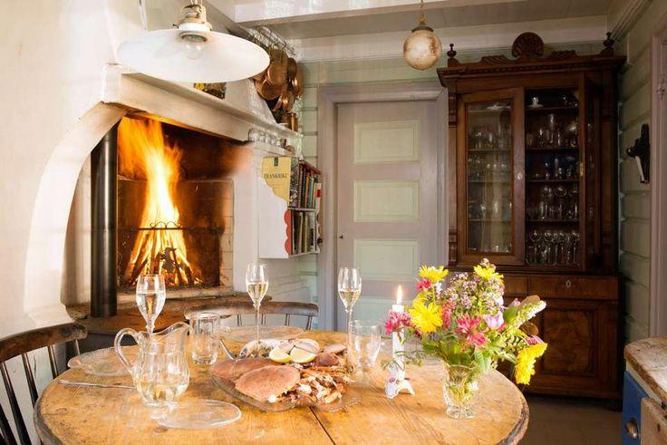 VEDFYRT KOMFYR: På kjøkkenet står ei grue med en 150 år gammel vedfyrt komfyr fra Gudbrandsdalen. Det utskårne bokskapet rommer en vakker samling av glass.