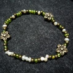 N°8 - bracelet élastiqué perles de nacre d'eau douce,perles de rocaille vertes irisées et perles et fleurs métal bronze