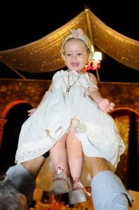 Happy little Christening Girl lifted in the air - Location Ktima Tritsimpida Greece - Summer Night - Photography Con Tsioukis - ICON PHOTOGRAPHY MELBOURNE - www.iconphotos.com.au