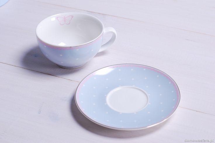 Filiżanka w formie gotowego prezentu, w wysokiej jakości kartonowym pudełku na prezent. Niebieskie naczynie jest ozdobione uroczymi białymi groszkami oraz różowymi falbankami. Wykończone połyskującym złotem na krawędziach. Idealny pomysł na stylowy prezent dla kobiety, która uwielbia kawę lub herbatę.