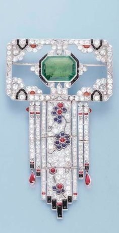 *AN ART DECO EMERALD AND DIAMOND BROOCH The central octagonal emerald within an onyx and diamond surround to the openwork rectangular panel and diamond fringe with cabochon sapphire and ruby floral detail and onyx terminals, circa 1925.