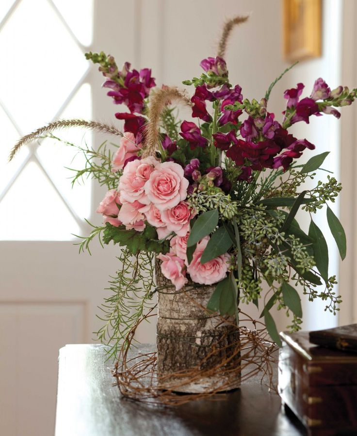 Rustic winter floral arrangement | Vase covered with birch bark sheet, twine & grapevine circlet | Spray roses, snapdragons, rosemary, kale, juniper, fountain grass