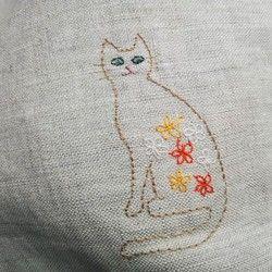ベージュのリネン生地に、猫の刺繍を入れました。小さめで、お財布と小物だけ入れてお出かけするのにぴったりです。内側は、ブルーの花柄生地を使っています。薄手の生地で、しわ加工のようなくしゃっとした手触りがあります。鍵など小物を入れるのに小さなポケットをつけました(スマートフォンは上半分が飛び出るのでおススメではありません)。写真4枚目に、手帳・小説・コインポーチを置いてみたので、参考にしてください。持ち手の長さは25cmくらいです。腕は入りませんので、手提げにして使うタイプです。大きさは横25cm、たて20cm、マチが5~6cm程度です。目安にしてください。少し折り畳んで良ければ、メール便(160円)で発送可能です。ラッピングや他の商品と同送の場合は、ヤマト運輸も可能です。ヤマト便は、通常より安価にご利用できます(関東500円~)。