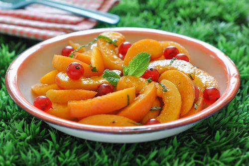 Les ingrédients pour préparer cette recette facile et rapide : des abricots, des groseilles, du sucre semoule, du sucre vanillé, un citron, des feuilles de menthe fraîche et de l'extrait de fleur d'oranger.