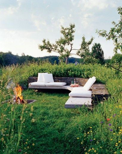 Outdoor seating are with an L-shaped bench topped with cream cushions and a built-in fire pit.