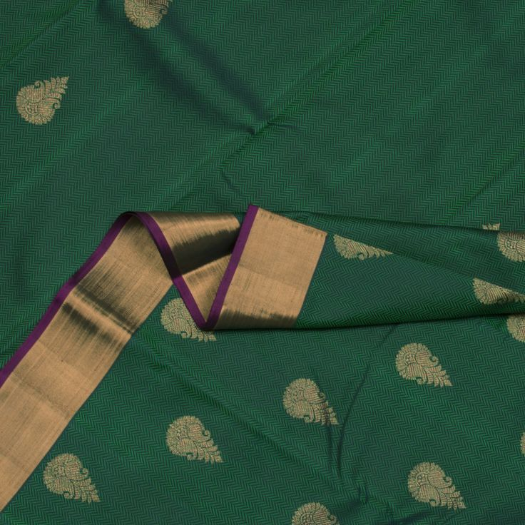 Vanki weaves and floral motifs adorn the bottle green body of this stunning Kanjivaram Sari. The purple pallu features a shimmering spread of zari motifs. A purple blouse completes the sari.