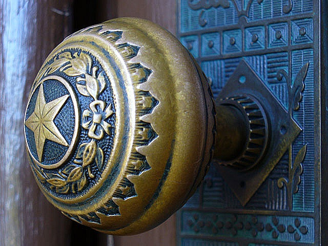 Capitol Doorknob    Detail photo of an ornate doorknob at the south entrance of the Texas state capitol. Blue highlights nicely mimic the blue patina in the brass plate.