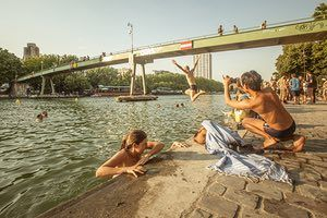 A swimmer waves at passersby, above him on a footbridge, while a friend pulls themselves up and out of the canal in east Paris. If you swim in the Seine the police arrive, quickly. There are cameras everywhere. Fortunately, our French culture has taught us to fight with authority but we don't want to have any trouble with police, so the best places are the canals on the outskirts of Paris where the police sometimes leave us alone to enjoy these beautiful waterways.
