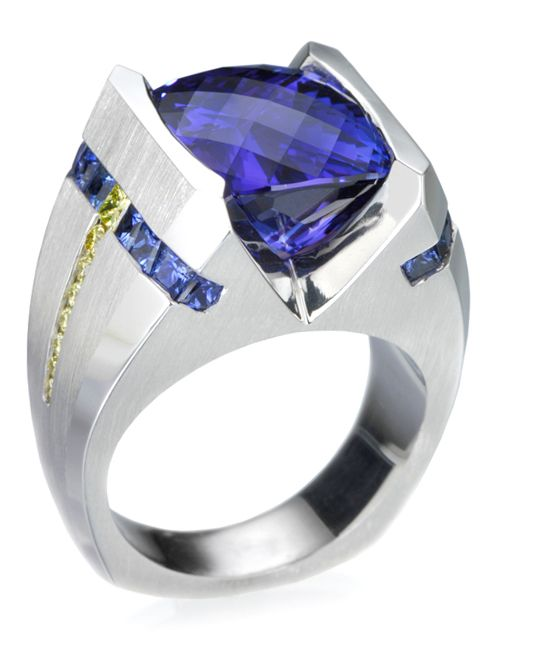 18k white gold gents ring featuring a 11.84ct tanzanite, 1.70ctw blue sapphires, and 0.43ctw of yellow diamonds.