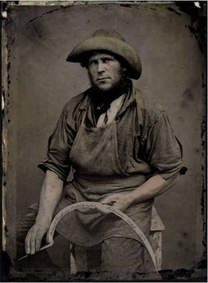 """ca. 1857, [tintype portrait of a farmer with his sickle], handwritten on the sickle's blade: """"Samuel Renshaw, Sicklegrinder Ridgeway, August 1857"""""""
