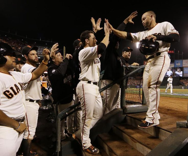San Francisco Giants Juan Perez, right, is congratulated after hitting two-run RBI double during the eighth inning of Game 5 of baseball's World Series Sunday, Oct. 26, 2014, in San Francisco. The Giants defeated the Royals 5-0 to lead the series 3-2 games.(AP Photo/David J. Phillip)