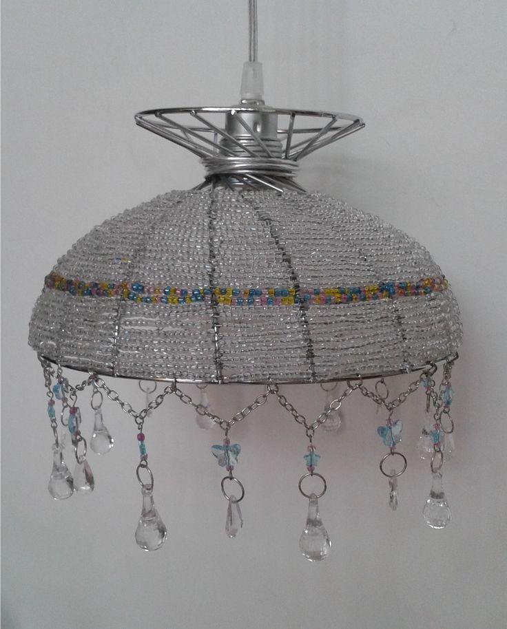Esta lámpara la hice utilizando como base un recipiente para frutas de metal. Los materiales que utilicé: alambre, mostacillones, cadenas, cuentas transparentes, argollas y caireles.
