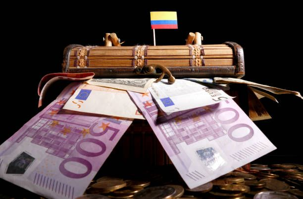 colombian flag on top of crate full of money
