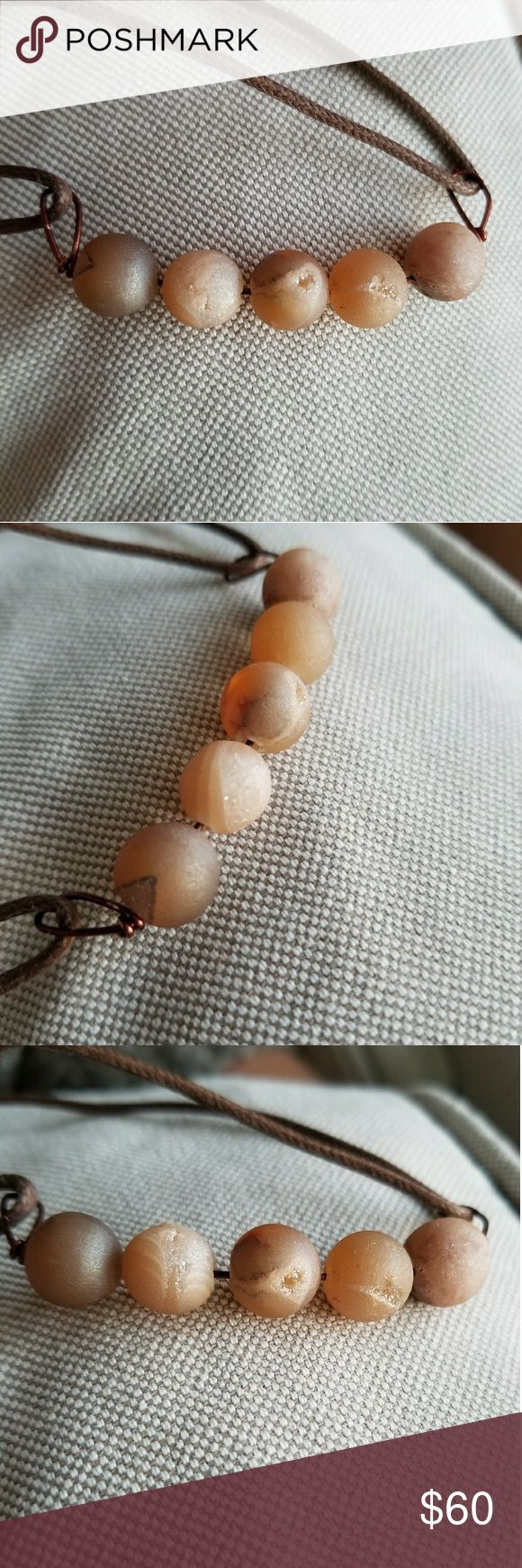 Rose Stone (Convertable) Necklace Five gorgeous, sparkly rosy stones make for a soft and earthy necklace. The surfaces of each sphere swirl with hints of gray, creamy white, and slightly glittery pale pinks. Currently on a brown fabric adjustable cord.   Picture provided of the current necklace length. May be converted into a bracelet by loosening/tightening the cord and wrapping around your wrist.   🌹Bundle your likes for bigger savings!🌹 Jewelry Necklaces