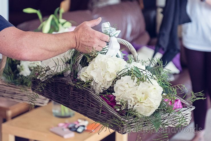 White wedding flowers in wicker basket on wedding morning in Dorset. Photography by one thousand words wedding photographers