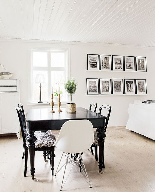 These #blackandwhite #photographs are beautifully #framed and displayed in this open dining room / living room space.  Love this look!