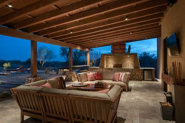 A covered outdoor kitchen and lounge a barbecue, bar and fire pit.