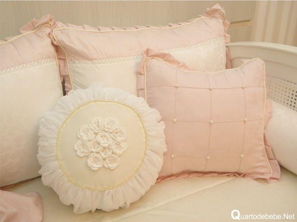 Enxoval de quarto de bebê rosa com flores e pérolas. A almofada decorativa conta com flores 3d e várias pérolas envolvendo-as.