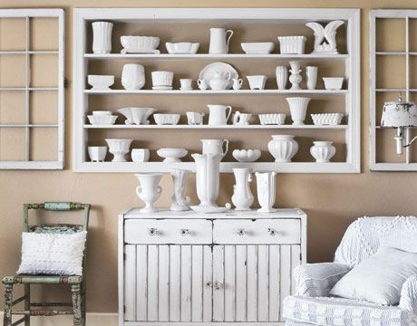 Like monochrome, formal arrangement by bookending the display shelf. Shelf could be designated solely for family photos.  Maybe with a sprinkling or punctuation of sentimental decor or books. Even hang small photos or pic on the wall inside the shelves.  Can you say finally, a place for milk glass?