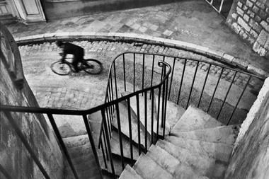 This image taken by Henri Cartier Bresson captures line from the left hand corner leading the eyes down the stairs to the movement by the person on the bike.