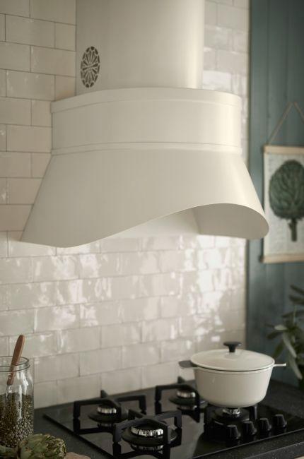 Witte keuken met een grote beige afzuigkap boven een gaskookplaat en een beige oven