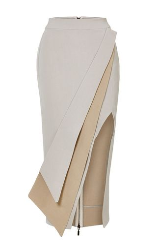 This **Maticevski** skirt features a pencil styled silhouette, a panel overlay front detail, and an exaggerated front slit.