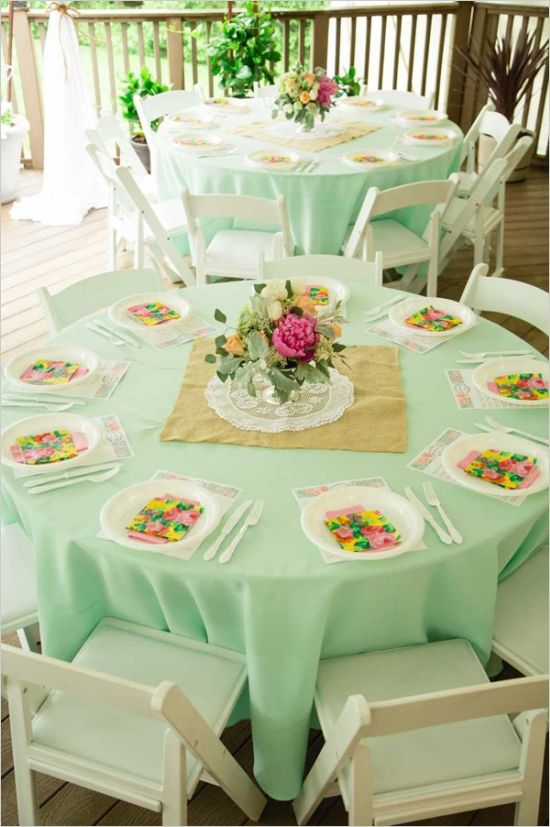 turquoise tablecloths, square mirror with lace doily on top, glass with one flower floating and two small candles on each side