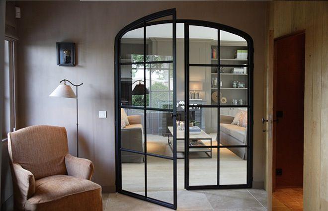 Landelijke inrichting met stalen raam als ingang naar de woonkamer - > me like voor tussen woonkamer en keuken...