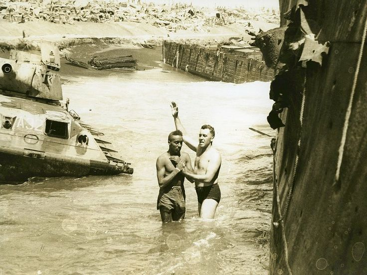 """John Craven Performs a Baptism at Iwo Jima, 1945. """"Chaplain John H. Craven, Regimental Chaplain, 14th Marines baptizes soldiers from the Army's 476th Amphibious Truck Company in the surf at Iwo Jima. """"Ducks"""" from this company carried the 14th Marines from LST's to the beach at Iwo."""""""