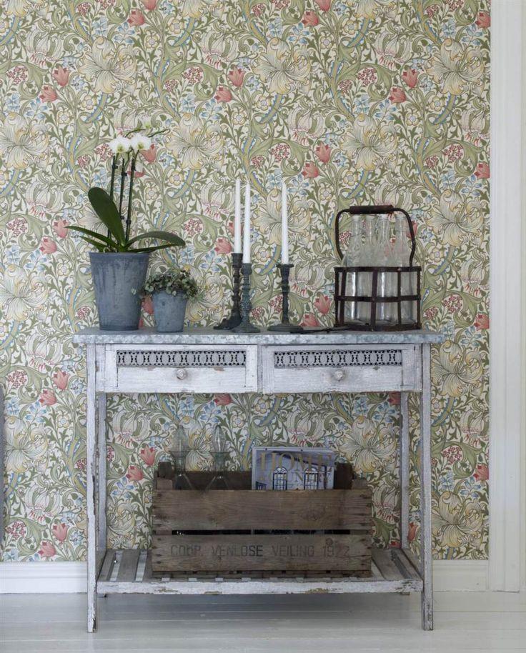 Det snygga avlastningsbordet i plåt från Caesars hem skapar en skön stilmix med den blommiga tapeten Golden Lily pale biscuit från William Morris