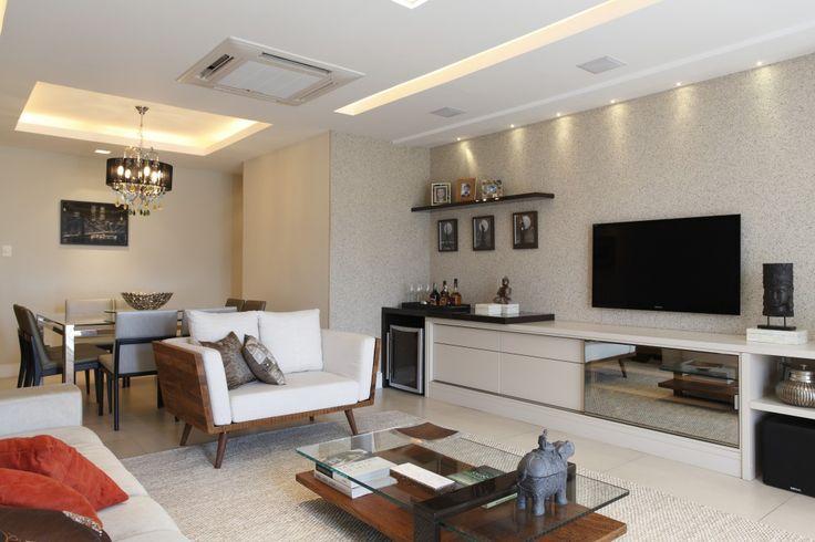 Sala em três ambientes, onde o aparador do sofá tem a função de delimitar o espaço home do estar. A Bontempo compõe o mobiliário com brincadeira de cores e texturas nas gamas do cinza e roxo. O bar da sala de estar se integra com o home em móvel Bontempo que abriga aparelhos eletrônicos. O sofá, com acentos retrateis complementa o espaço versátil que harmoniza madeira de demolição da mesa de centro e poltrona com a leveza das cores contemporâneas