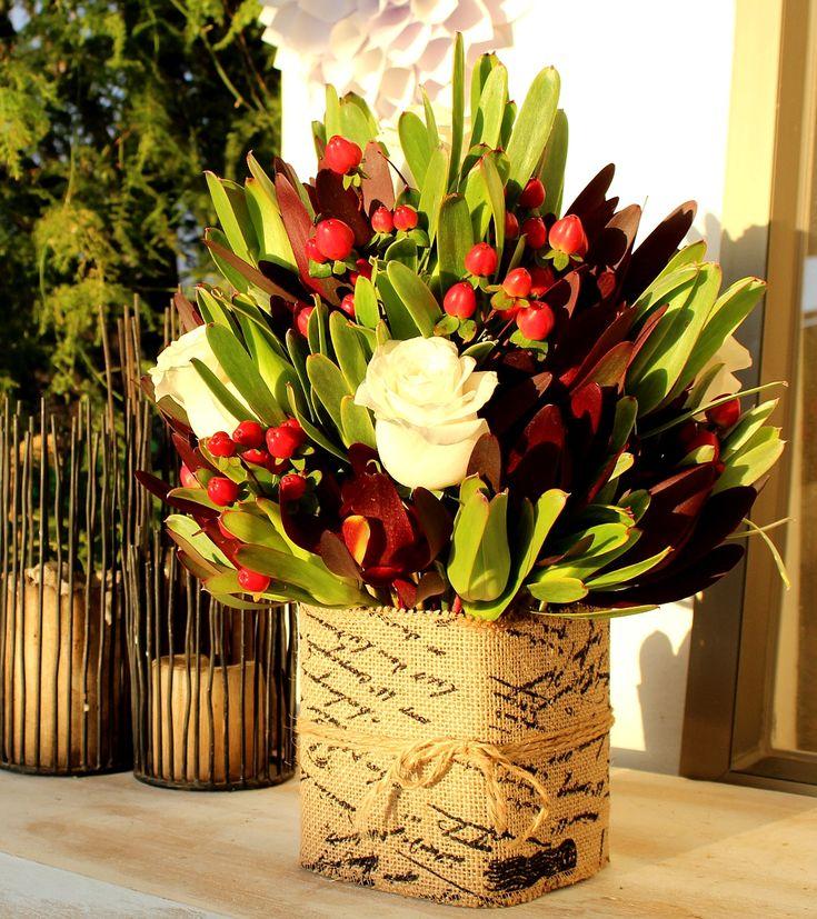 Rosas, leucadendro e hypericum envueltos en arpillera impresa.