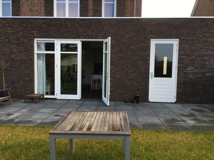 Achtergevel huis: links openslaande deuren naar woonkeuken, rechts garagedeur.
