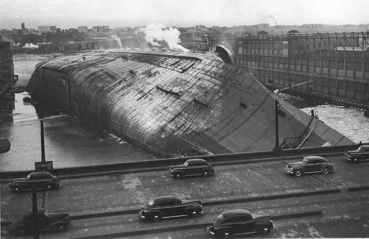 French liner SS Normandie after she caught fire and capsized. Pier 88 NYC, 1942