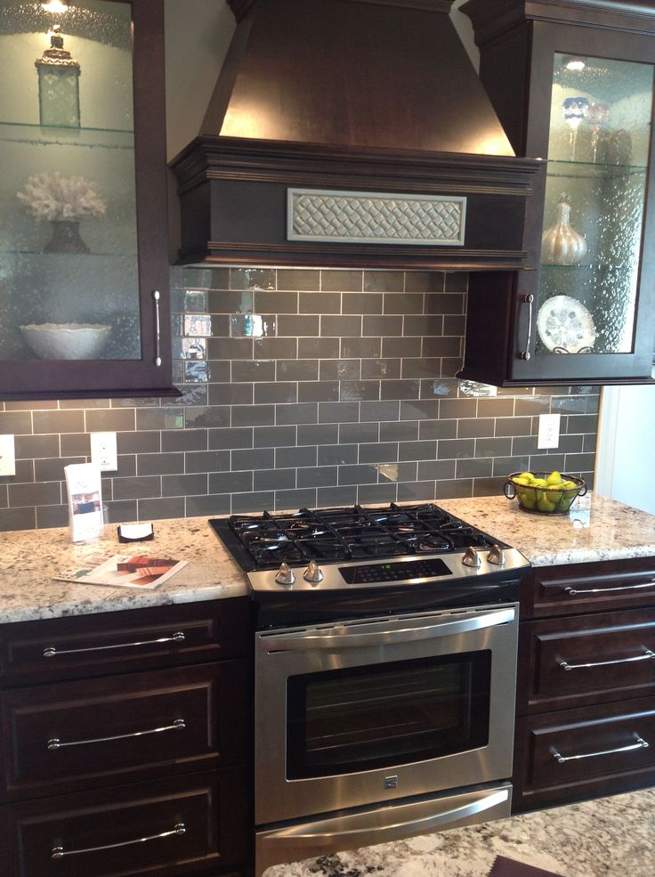 'Ice' gray glass subway tile backsplash with dark brown cabinets and stainless steel appliances.