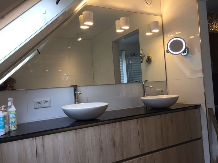 Badkamer meubel gemaakt van keuken kasten met schuin dak. Maatwerk spiegel met lampen erop van lamp en licht. Blad van composiet met twee opzet kommen en kranen van Luca sanitair