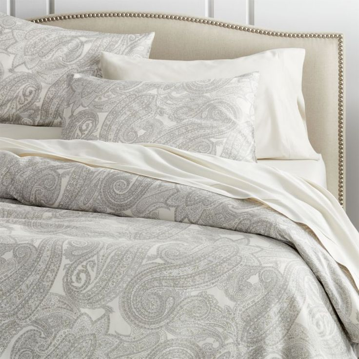 Mariella bed linens modernize the traditional paisley pattern in tonal grey and cream. Made in Italy, the silky cotton sateen fabric is printed with an exclusive color vat print method that preserves the quality and color wash after wash, year after year. A special finish applied during the final stages of production reduces wrinkles after washing. Duvet cover holds an insert in places with inner-corner ties and is detailed with a button closure. Shams have overlap closures. <a…