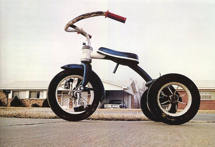 "William Eggleston, Memphis (Tricycle)', 1970. ""...Homely objects had a long tradition of being photographed— [but] Eggleston's tricycle is different. It's at once beneath homeliness yet oddly exalted. One way Eggleston achieves this effect is obvious: he shoots the tricycle from a low angle. It looms large in the imagination because it looms large, period. Looking heavenward, Eggleston's camera bestows on that tricycle the majesty—and ineffability—of an archangel's throne:"""